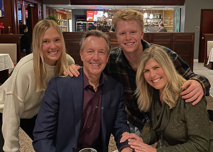 Doctor Olson with his family in a restaurant smiling