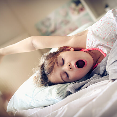 A child yawning in bed