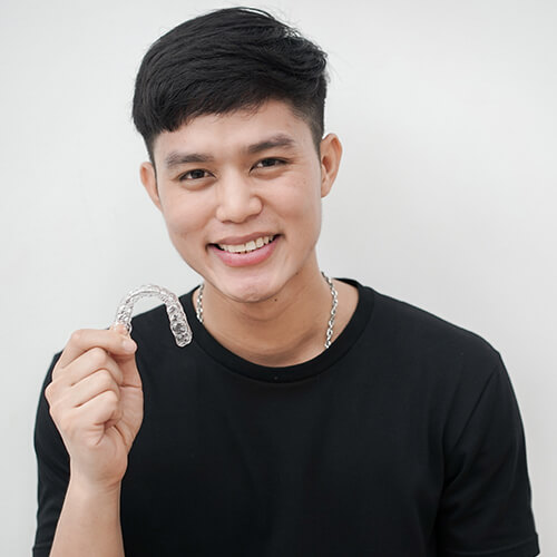 A young man holding Invisalign clear aligners