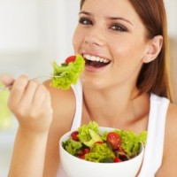 A smiling woman eating salad