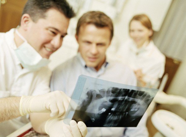 A dentist examining a dental X-Ray