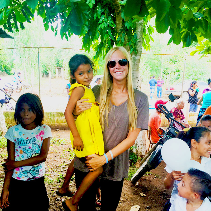 Kelsey Olson Holds little girl in a yellow dress from guatemala