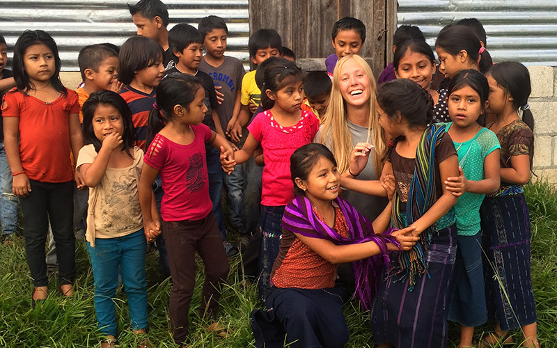 Kelsey Poses with all the children that are having a school built for them
