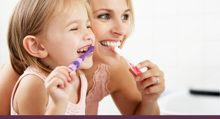 Mom and little daughter brushing their teeth while they look in a mirror.
